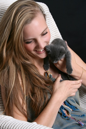 Young blond teen holding a grey kitten photo