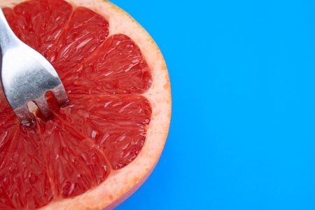 Sliced grapefruit on a blue background with fork
