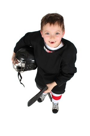 Young boy in ice hockey gear against white