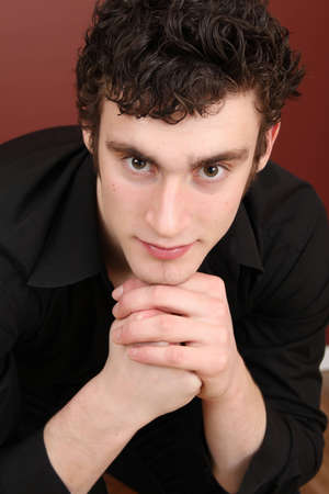 Attractive brunette male model against dark red background photo