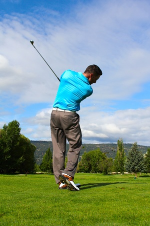 Young golfer hitting a shot with an iron photo