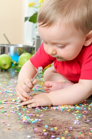 baby cutlery: Cute baby boy eating cake decorations on counter top