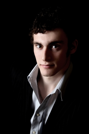 Attractive male model on a black background with uneven lighting effect photo