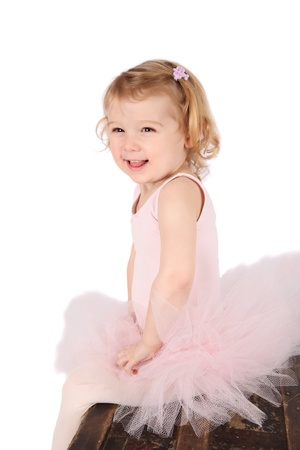petite girl: Little ballet girl wearing a pink tutu on an antique trunk Stock Photo