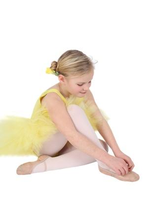 petite girl: Blond girl wearing a yellow ballet tutu on white background Stock Photo