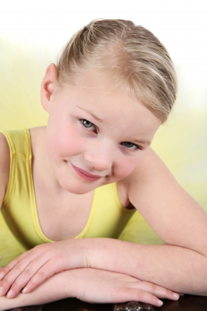 petite girl: Blond girl wearing a yellow ballet tutu on white background Stock Photo