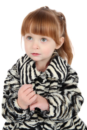 Little girl wearing a winter coat against white