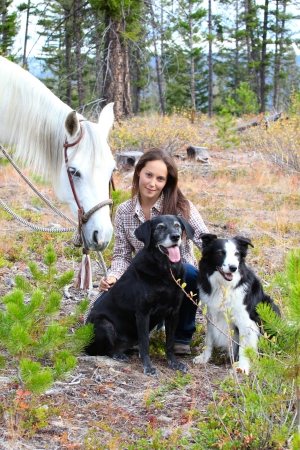 Beautiful brunette cowgirl with her horse and dogs Stock Photo - 23550648