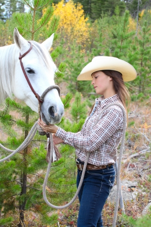 Beautiful brunette cowgirl with her horse on a mountain trail ride Stock Photo - 23550678
