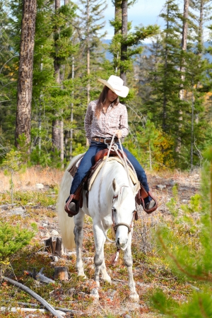 Beautiful brunette cowgirl with her horse on a mountain trail ride Stock Photo - 23550680