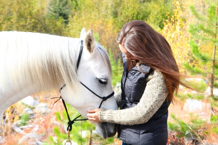 Beautiful young brunette cowgirl with her white horse Stock Photo - 23550683