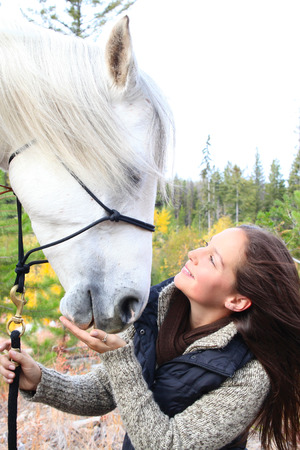 Beautiful young brunette cowgirl with her white horse Stock Photo - 23550686