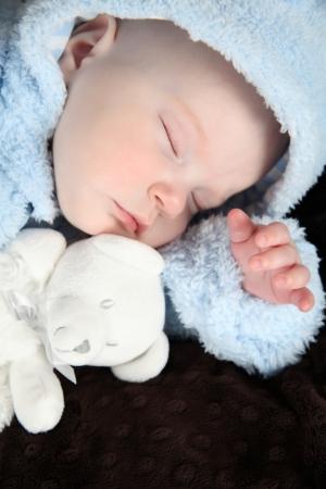 warmly: Sleeping baby boy wrapped warmly with his teddy bear Stock Photo