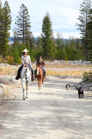 Beautiful brunette cowboy and cowgirl on a mountain trail ride photo