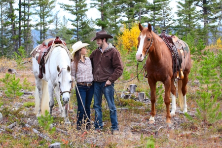 Cowboy e cowgirl in montagna con i loro cavalli photo