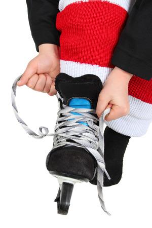 ni�os vistiendose: Muchacho joven que ata sus patines de hielo en hockey uniforme