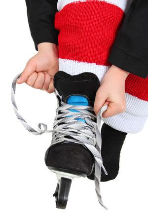kids feet: Young boy tying his Ice Skates in hockey uniform Stock Photo
