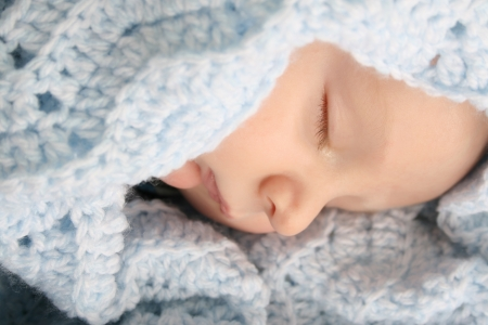 Sleeping baby boy wrapped in a wool blanket photo