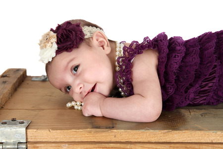 romper: Brunette baby girl wearing a purple romper with pearls Stock Photo
