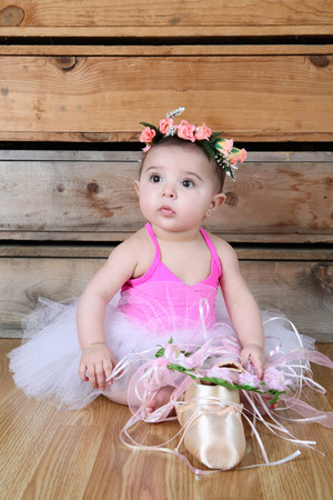 little girl dancing: Baby ballerina wearing a white tutu and pink bodysuit