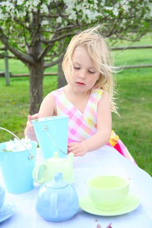 Little blond girl having a garden tea party Banco de Imagens