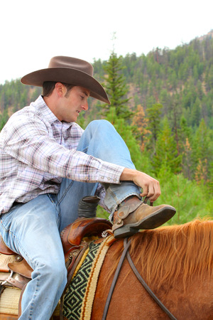 Young cowboy riding his horse in the field  Stock Photo