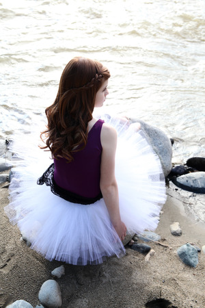 Beautiful girl wearing a white tutu by the river photo