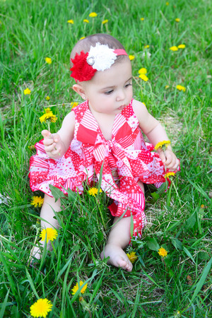Brunette baby sitting in a field with dandelions photo