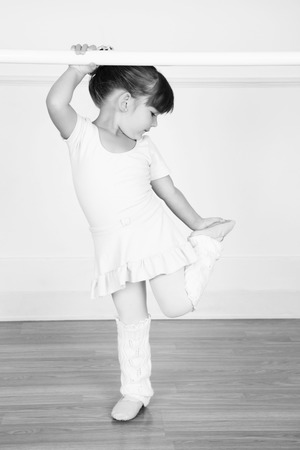 Beautiful little ballet dancer at the dance studio barre