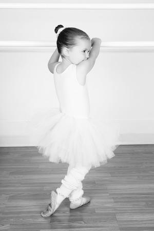 barre: Beautiful little ballet dancer at the dance studio barre