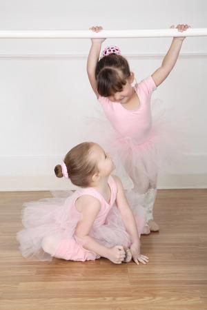 Hermosas poco bailarines de ballet en el estudio de danza barre