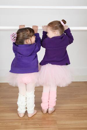 barre: Beautiful little ballet dancers at the dance studio barre