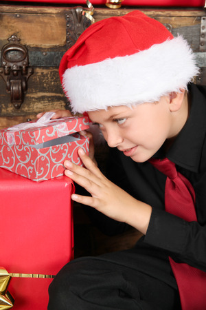 finding out: Young boy excited about finding out what his gift is Stock Photo