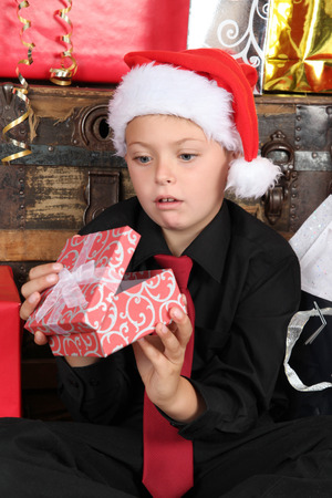 dissapointed: Young boy wearing a christmas hat dissapointed with gift