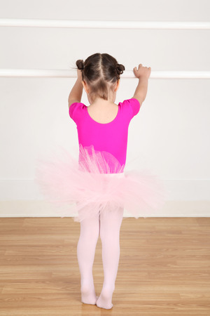 barre: Toddler ballerina standing on her toes by the barre