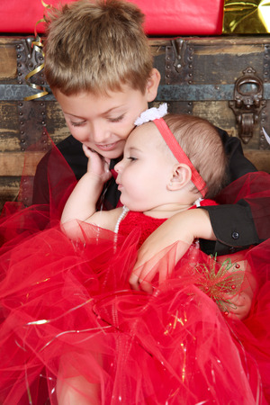 Young boy with his baby sister at christmas time photo