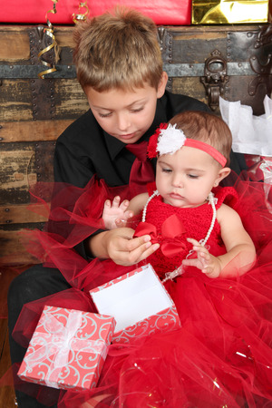 Young boy with his baby sister opening a gift box photo