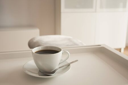 a cup of coffee on a tray in a living room Foto de archivo