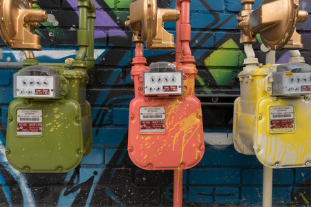 Colorful gas meters splattered with yellow, orange, green paint on a graffiti blue background.