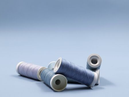 Sewing threads, blue spools of thread on a blue background. Room for copy.