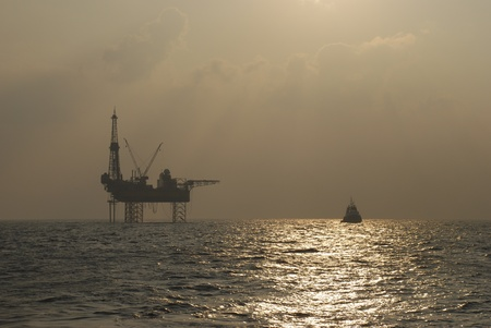 Oil rig with standby boat in the sunset Stock Photo
