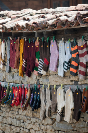 woolen: Hanging woolen socks on fence facade.