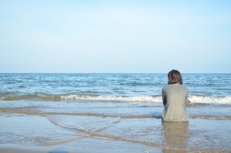 the girl is sitting alone at the beach and looking through the sea
