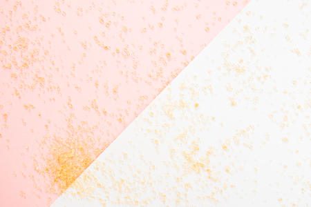 granules: Close up of brown sugar granules on white and  soft pink background