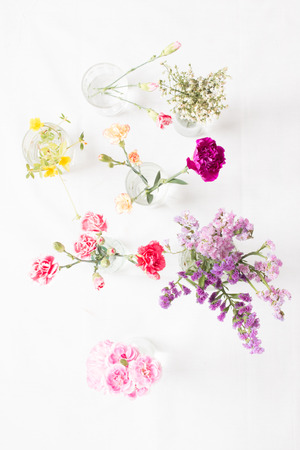 Top view of various flowers on white fabric background.