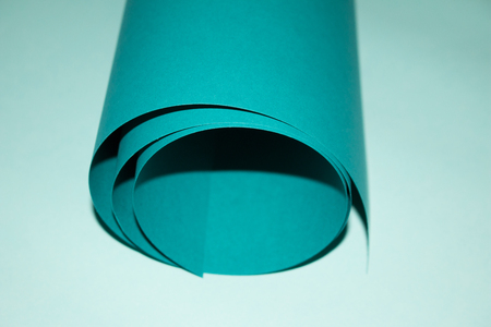 blue green background: Roll green paper on blue background.
