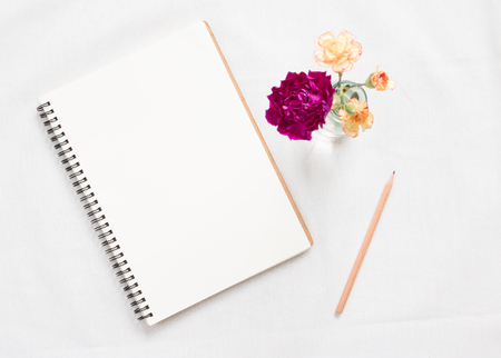 Top view of blank notebook and flower on white workspace background. Focus notebook. Stock Photo