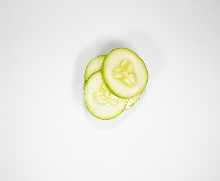 Topview of slices cucumber isolated on white background.