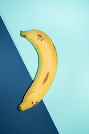 two tone: Banana on two tone blue background.