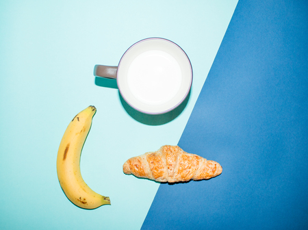 two tone: croissant, milk and banana on two tone background. Stock Photo